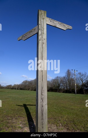 Wooden footpath signpost against clear blue sky - Stock Photo