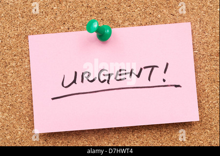 Urgent word written on paper and pinned on cork board - Stock Photo