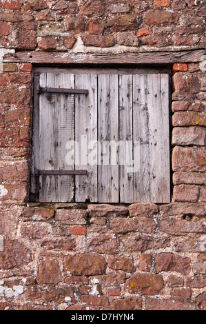 stone wall, old, wooden door, weathered, unpainted,old natural stone wall, pointing, mortar joints,old iron hinges, - Stock Photo