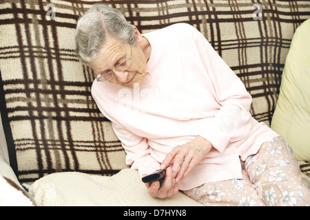 Elderly woman using a specialised big button telephone phoning the 111 non emergency medical advice helpline due - Stock Photo