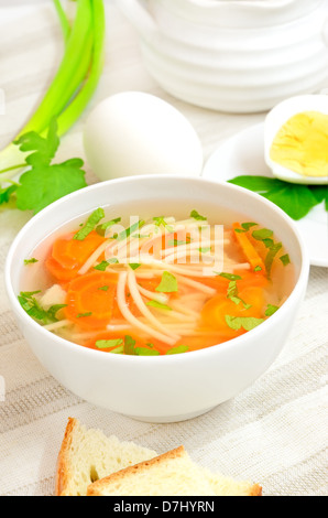 Soup with pasta and vegetables in white bowl on a table - Stock Photo
