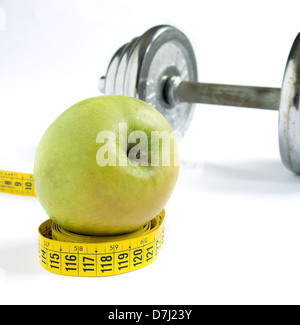 green apple on a yellow tape with a metal dumbbell in the background - Stock Photo