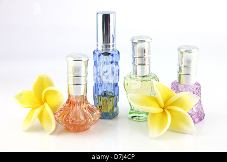 The yellow flowers and Orange,Blue,Green,Violet Perfume bottles on the white background. - Stock Photo