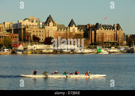Dragon boat rowers practicing in Inner Harbor with Victoria skyline and Empress hotel-Victoria, British Columbia, - Stock Photo