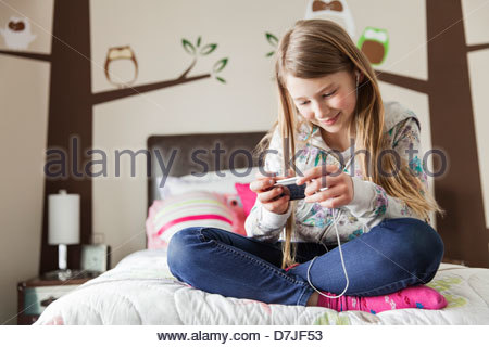 Young girl with headphones listening to music on bed - Stock Photo