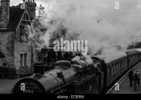 Black and white image of Swanage Railway steam train arriving at Corfe Castle village, a National Trust location in Dorset, UK.
