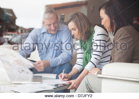 Senior couple signing documents with financial advisor at home - Stock Photo