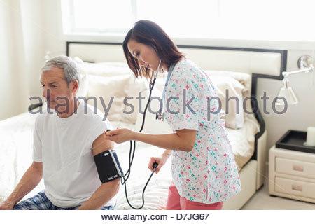 Female nurse checking blood pressure of senior man at home - Stock Photo
