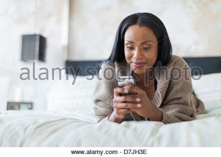 Woman using mobile phone while lying on bed - Stock Photo