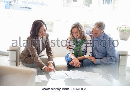 Female financial advisor explaining contract to senior couple at home - Stock Photo