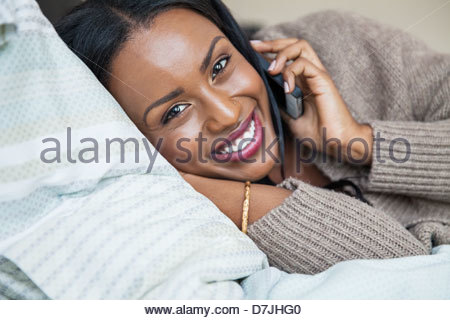 Portrait of woman using mobile phone while lying on bed - Stock Photo