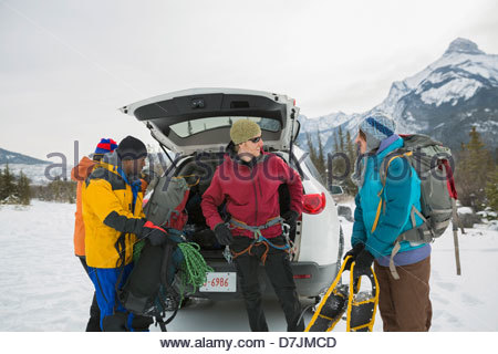 Group of friends preparing for snowshoeing in mountains - Stock Photo