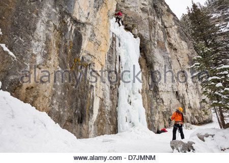 Man belaying friend on ice wall in mountains - Stock Photo