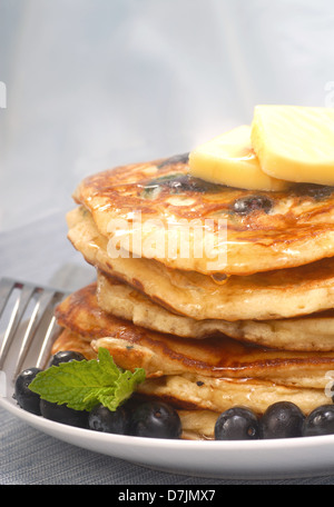 Delicious homemade blueberry pancakes with pure maple syrup dripping down them - Stock Photo