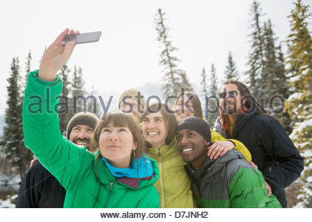 Group of friends taking self portrait with mobile phone in mountains - Stock Photo