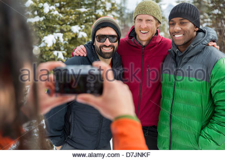 Man taking photograph of friends outside in winter - Stock Photo
