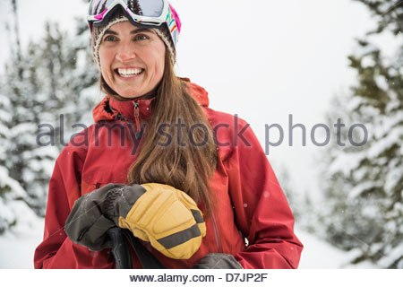 Smiling woman backcountry skiing in mountains - Stock Photo