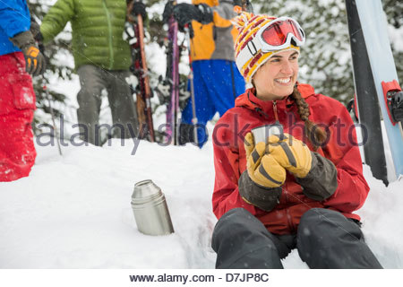 Female skier having coffee in snow with friends standing in background - Stock Photo