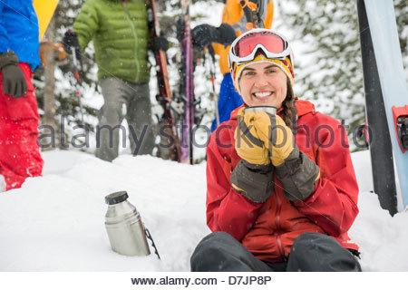 Portrait of female skier having coffee in snow with friends standing in background - Stock Photo
