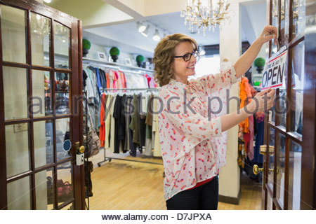Female small business owner hanging 'open' sign on front door - Stock Photo