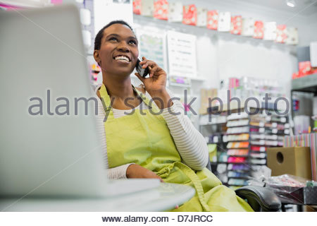 Female small business owner talking on phone in store - Stock Photo