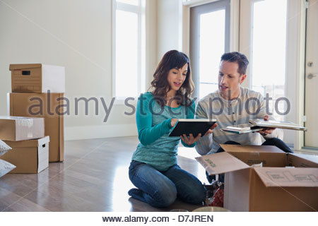 Couple unpacking cardboard boxes in new home - Stock Photo