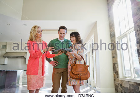 Female realtor showing brochure to couple in new home - Stock Photo