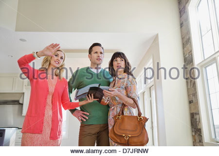 Female realtor showing new home to couple - Stock Photo