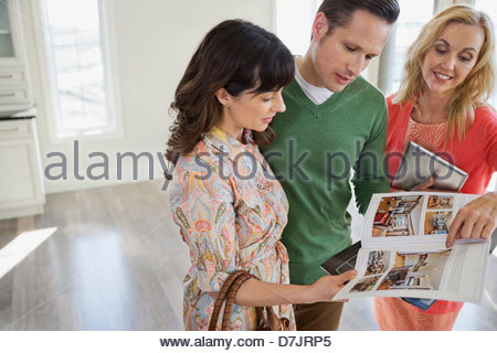 Female realtor showing new home brochure to couple - Stock Photo