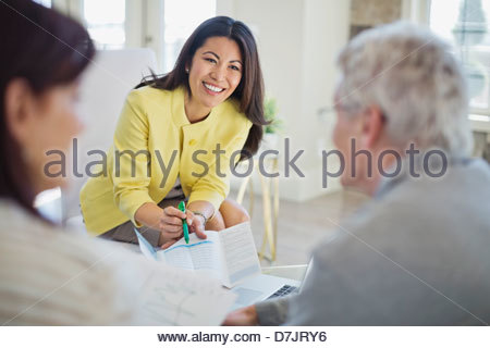 Female financial advisor working with couple in home - Stock Photo