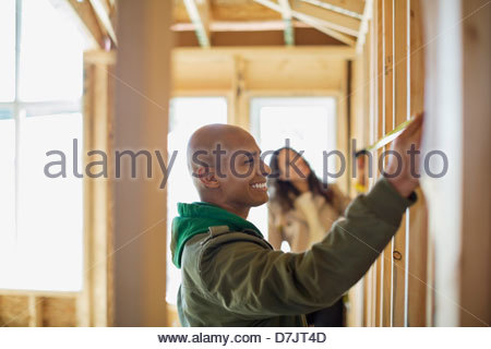 Young couple measuring wall at new home construction site - Stock Photo