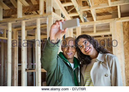 Young couple taking photographs in new home construction site - Stock Photo