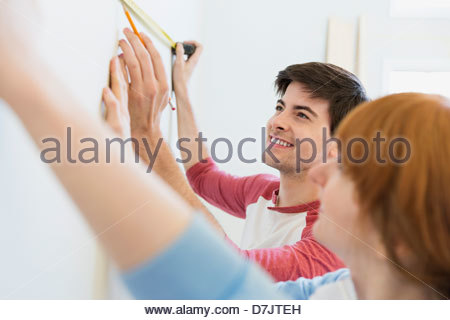 Young couple measuring wall in home - Stock Photo
