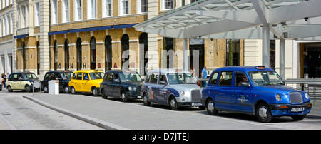 London taxis queuing at taxi rank showing the changing outward appearance of the standard black cab - Stock Photo