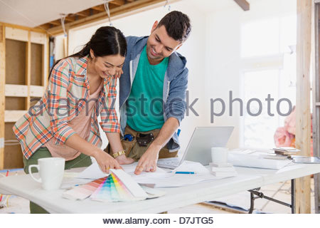 Couple discussing home designs in kitchen - Stock Photo