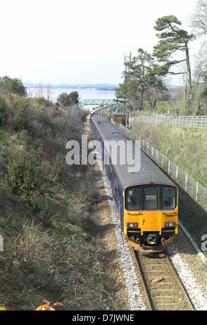 First Great Western train on the Exeter to Exmouth railway with the river Exe behind - Stock Photo