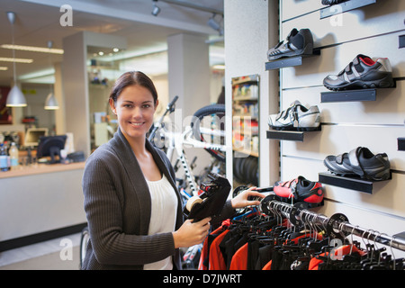 Business owner pricing sportswear in store - Stock Photo