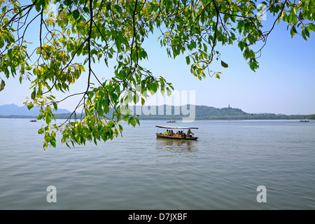 Tourists in traditional row boats on West Lake, Hangzhou - Stock Photo