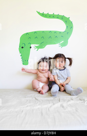 Two cute Korean American kids sitting on bed posing for camera in front of crocodile wall art Stock Photo