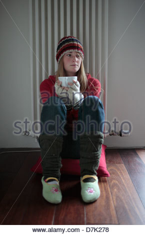 Young woman sitting in front of a radiator and having coffee - Stock Photo