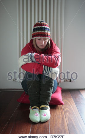 Young woman sitting in front of a radiator and looking sad - Stock Photo