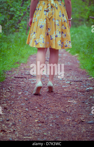 legs of a woman in a yellow dress walking on a path in the woods - Stock Photo