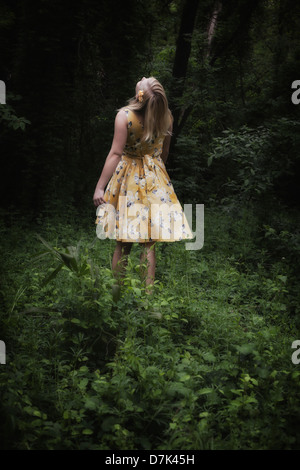 a blond girl with a yellow dress is dancing in the woods - Stock Photo