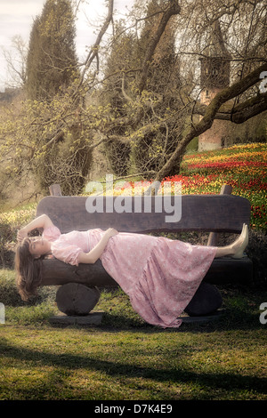 a woman in a floral dress is lying on a bench in a parc - Stock Photo