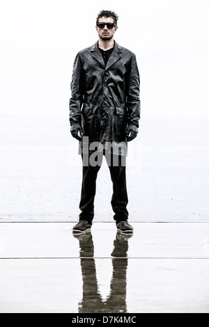 a sinister man in a black, wet leather jacket during rain - Stock Photo