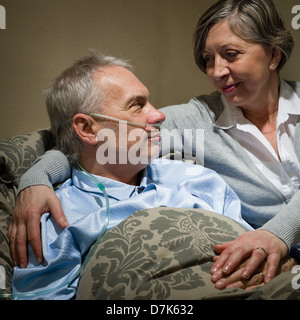 Seriously ill old man lying in bed with loving wife - Stock Photo