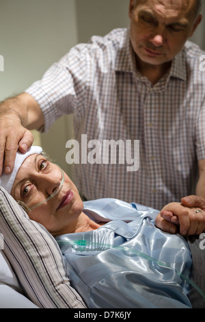 Loving husband taking care of seriously sick mature wife - Stock Photo