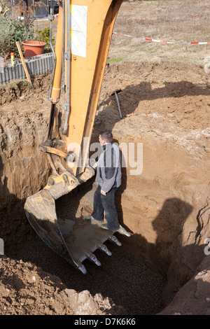 Europe, Germany, Rhineland Palatinate, Mature man working in pit for installing cistern of rainwater - Stock Photo