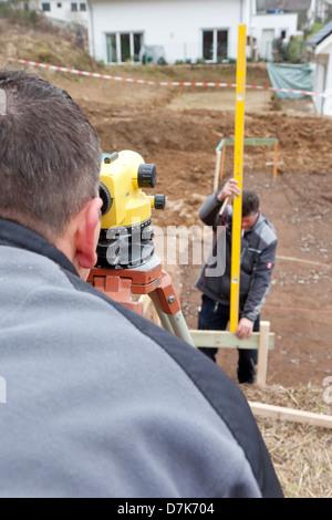 Europe, Germany, Rhineland Palatinate, Mature men measuring land for foundation - Stock Photo