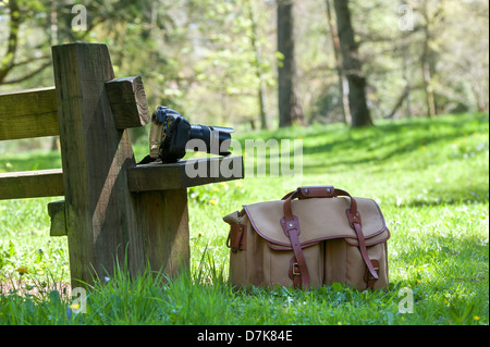 Nikon Camera equipment and bag on a seat in an English woodland - Stock Photo